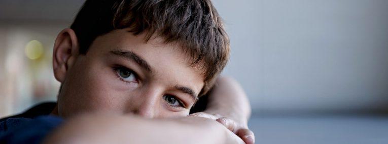 Junge traurig auf dem Tisch liegend